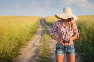 openluchtportret van jonge aantrekkelijke vrouw met retro camera