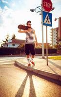 stijlvolle man in zonnebril met een skateboard op straat