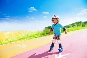 gelukkige jongen die bergafwaarts rent op rolschaatsen