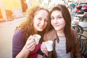 meisjes die Italiaans traditioneel ontbijt hebben bij bar foto