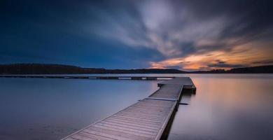 mooi lang belichtingsmeer met steiger bij zonsondergang.