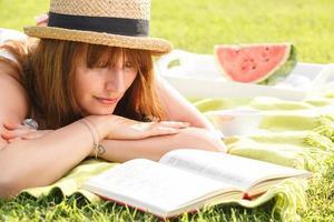 aantrekkelijke jonge vrouwelijke leesboek in het park