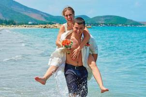 gelukkige bruid en bruidegom lopen op een prachtig tropisch strand foto
