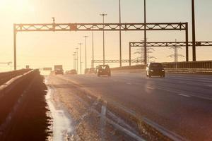 stadsringweg bij zonsondergang met silhouetten van rijdende voertuigen