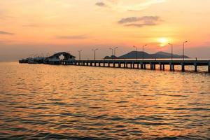 zonsondergang achter klein havenschip en lantaarnpaal