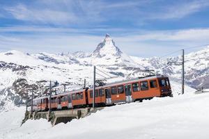 de trein die met matterhorn naar het station rijdt. foto