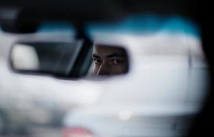 man kijkt in de achteruitkijkspiegel tijdens het rijden foto