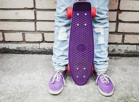 tienermeisje in spijkerbroek houdt een skateboard