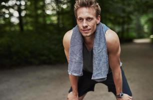 atletische man rusten na het joggen in het park