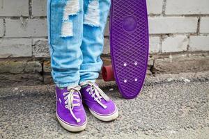 tiener in spijkerbroek staat met skateboard