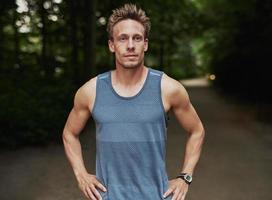 atletische man in het park met handen op de taille