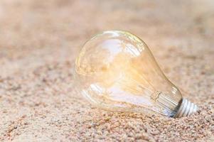 gloeiende gloeilamp in het zand foto