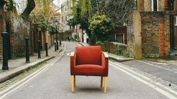 Londen, Verenigd Koninkrijk, 2020 - versleten rode stoel in straat