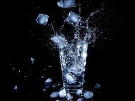 ijsblokjes vallen in een heldere drinkbeker met water