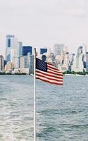 usa vlag op paal dichtbij zee onder bewolkte hemel