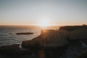 zonsondergang op rotsen en kliffen naast zee