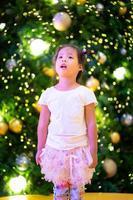klein Aziatisch meisje en bokeh achtergrond op eerste kerstdag