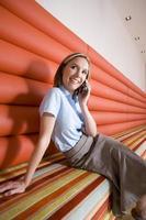 zakenvrouw op mobiele telefoon op bankje, glimlachend