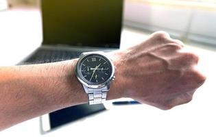 zakenman die op zijn horloge kijkt