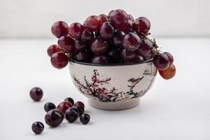druiven in een kom op neutrale achtergrond foto