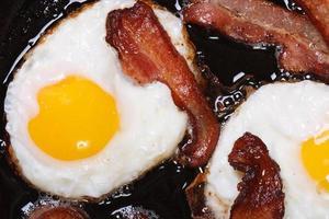 gebakken eieren met spek in een pan bovenaanzicht