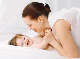 gelukkige moeder en baby plezier in bed thuis