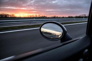 uitzicht vanuit een autoraam tijdens het rijden tijdens zonsondergang foto