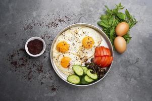 presentatie van gebakken eieren met pepermuntjes, tomaat, olijven, komkommer en sumak