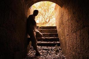 jonge man staat in donkere stenen tunnel foto