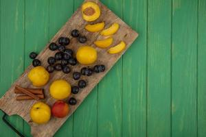 geassorteerde fruit op snijplank op groene achtergrond
