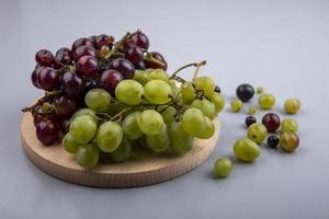 geassorteerde druiven op snijplank op grijze achtergrond foto