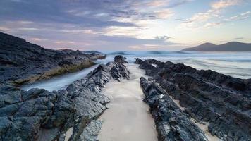 rotsachtige kust onder een gedempte zonsondergang