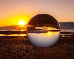 lensball op zand bij zonsondergang