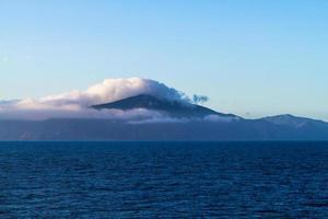 berg bedekt met mist in de buurt van de oceaan