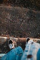 persoon in spijkerbroek en zwarte sneakers die op de stoep staan