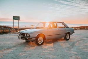 Kaapstad, Zuid-Afrika, 2020 - grijze BMW sedan voor ondergaande zon