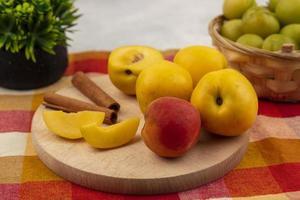 perziken op een houten bord op de achtergrond van een gecontroleerd tafellaken foto