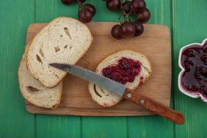 gesneden brood met frambozenjam op groene achtergrond