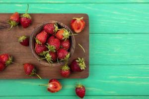 aardbeien op een houten bord op groene achtergrond met kopie ruimte