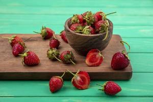 aardbeien op een snijplank op een groene achtergrond foto