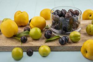 geassorteerde fruit op een snijplank en een blauwe achtergrond foto