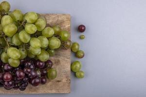geassorteerde druiven op grijze achtergrond met kopie ruimte foto