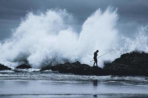Sydney, Australië, 2020 - silhouet van een man met een hengel die op een rotsachtige kust loopt