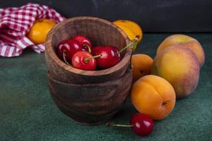 vooraanzicht van perziken met abrikozen en kersen in kommen foto
