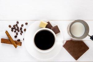 bovenaanzicht van een kopje koffie met kaneelstokjes foto