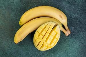 bovenaanzicht van bananen met gehakte mango's op een groene achtergrond