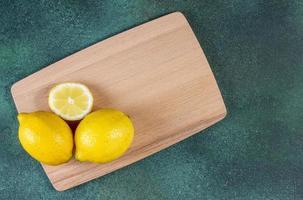 bovenaanzicht van citroenen op bord op groene achtergrond