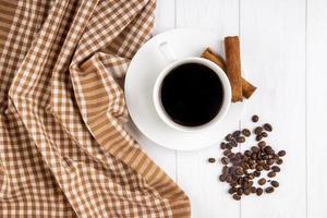 bovenaanzicht van een kopje koffie met kaneelstokjes
