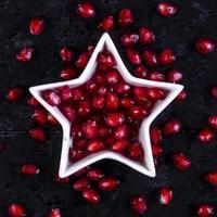 bovenaanzicht gepelde granaatappel in de vorm van een ster op een zwarte achtergrond