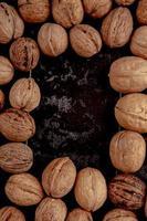 bovenaanzicht van hele walnoten verspreid over zwarte achtergrond met kopie ruimte foto